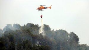 Pla tancat d'un helicòpter dels Bombers descarregant aigua en un incendi que s'ha originat a Picamoixons.