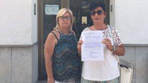 Dues veïnes mostrant el manifest entrat a registre a l'Ajuntament pel cessament de Martín Julio Grondona