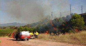 L'incendi crema una zona de vegetació propera a la via del tren