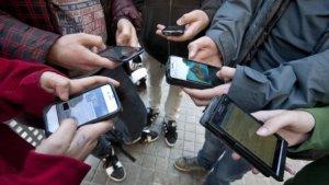 Grup d'adolescents amb telèfons mòbils connectats a les xarxes socials
