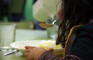 Imatge d'una nena menjant a un menjador escolar