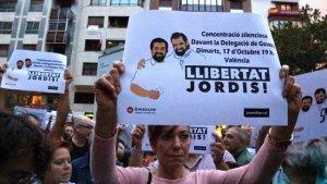 Una persona aixecant un dels cartells demanant la llibertat de Sánchez i Cuixart