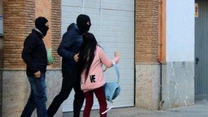 Agents dels Mossos emportant-se material i una detinguda