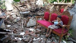 Un joven se toma su desayuno en su casa destruida después de un terremoto en Bantul, Indonesia.
