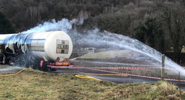 Imatge dels treballs d'extinció de l'incendi, ja controlat, que ha afectat la part inferior d'un camió cisterna amb gas a Les