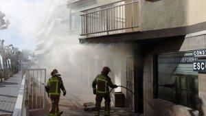 Dos Bombers extingint l'incendi de Cambrils aquest matí.