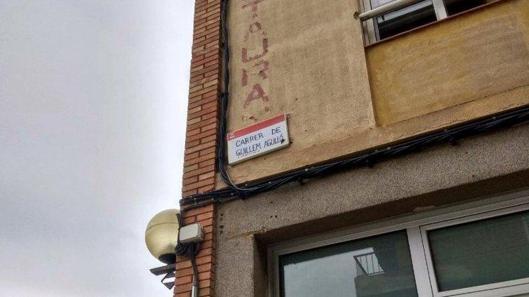 La placa amb el nom del carrer Josep Maria Fàbregas ha estat substituïda per la de Guillem Agulló.