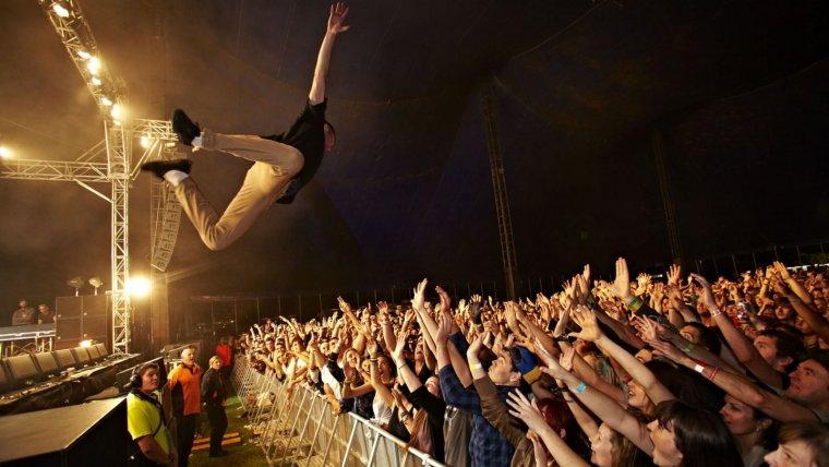 Un música hace stage diving durante un concierto.