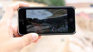 Detall d'una mà amb un iPhone a l'amfiteatre de Tarragona, on es pot veure com era el monument a l'època romana.
