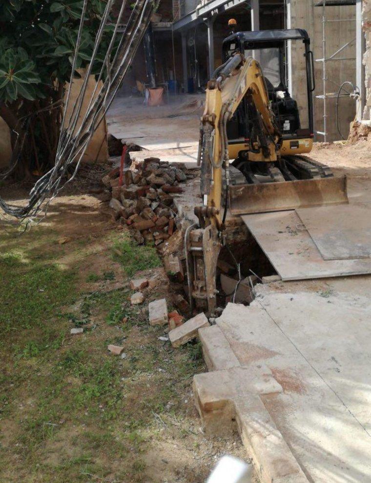 Una màquina treballant on hi havia hagut la paret mitgera