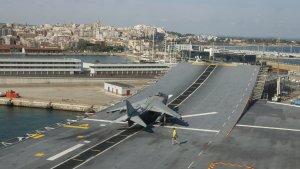Imatge de la coberta del portaavions Juan Carlos I amb la ciutat de Tarragona al fons