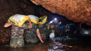 Diversos membres d'un equip de rescat intenten drenar l'aigua de la cova Tham Luang