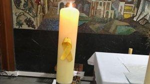 Un llaç groc penja d'una espelma de l'església de Sant Ramon Nonat de Coma-ruga