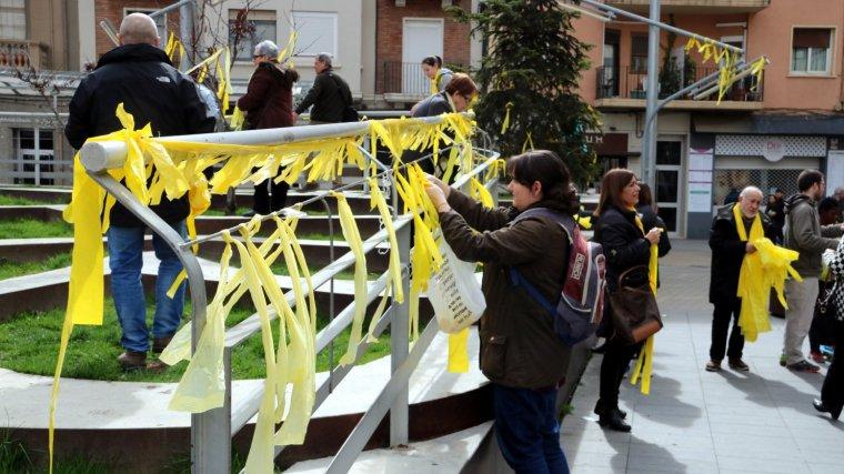 Imatge d'arxiu d'una persona col·locant llaços grocs.