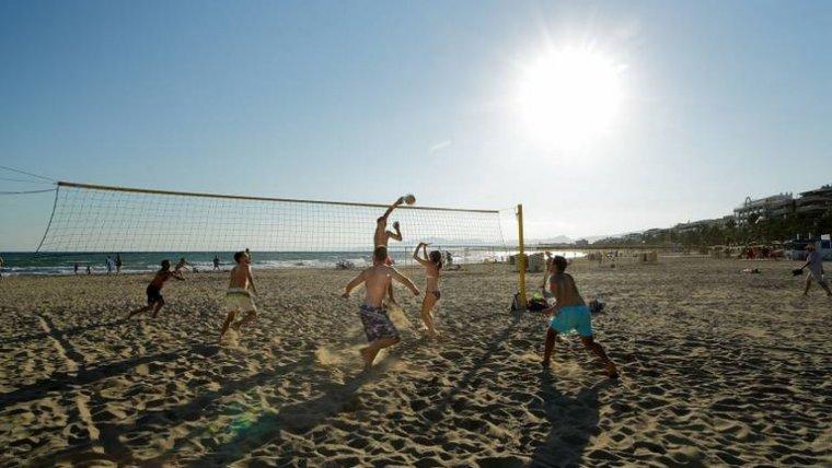 Joves jugant a vòlei platja a Salou.