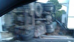 Imatge de la cabina de l'autocaravana, totalment bolcada, vista a través d'un altre vehicle