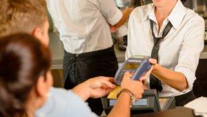 Imagen de una persona pagando con tarjeta de crédito en un establecimiento comercial.