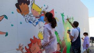Joan Turu i els alumnes de 6è de primària pintant el nou mural de l'esvola Ventura Gassol
