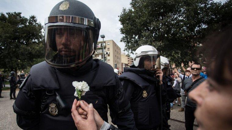 Una dona oferint una flor a un membre de la policia espanyola el passat 1-O