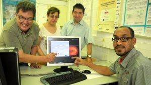 """El doctor Pere Romero amb el seu equip i el programa """"Retiprogram"""" en pantalla."""