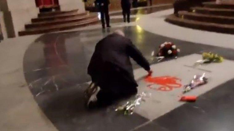 Moment en el qual l'home pinta de vermell la tomba de Franco