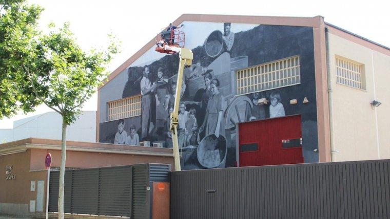 La façana de la fàbrica de Vermuts Miró amb el mural a punt de ser enllestit.