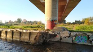 La passera de fusta que travessa el Francolí es troba al mig del riu i amb brutícia acumulada.