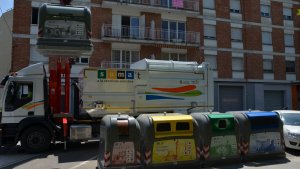 Un camió de la brossa buidant uns contenidors