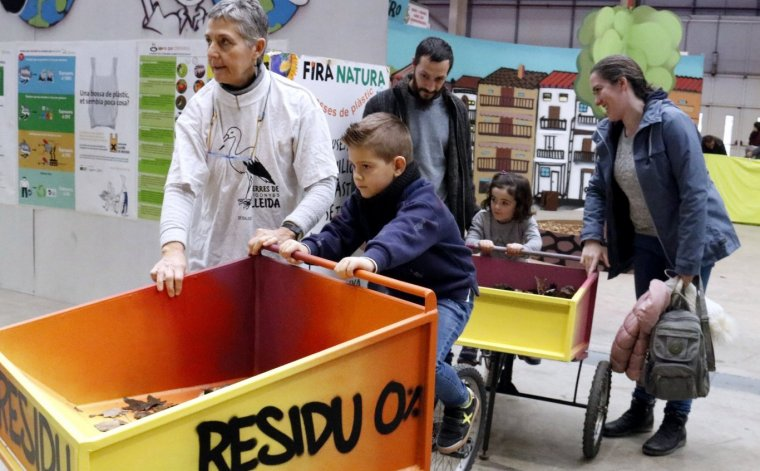 Infants amb els seus pares, participant a l'activitat de reciclatge al Cucalòcum