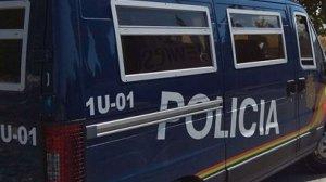 Algunos agentes de la Policía Nacional con un furgón