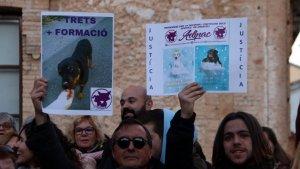 Dos manifestants alçant cartells reivindicatius en la protesta per la mort d'un rottweiler abatut per la policia a Calafell