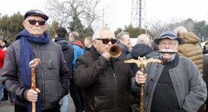 Pla mitjà on es poden veure tres jubilats d'Endesa protestant a les portes de l'estació de Lleida