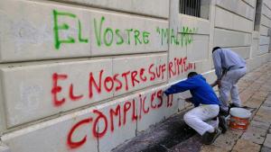 Operaris netejant les pintades a la façana del Palau Arquebisbal aquest dijous set de febrer