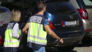 Dos agents de la policia espanyola traslladant un dels detinguts pel lloguer fraudulent d'apartaments turístics