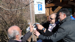 El conseller d'Interior, Miquel Busch, col·locant una placa que identifica un punt per trucar al 112