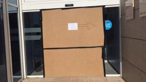 Imatge de la porta de l'Hospital Lleuger de Cambrils, trencada, amb elements de protecció