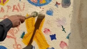 Imatge d'un agent dels Mossos traient una pintura de llaços grocs d'un mural