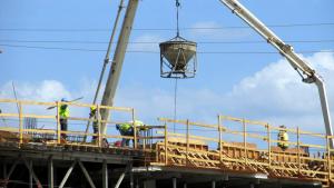 Pla contrapicat d'una grua i operaris treballant en una construcció