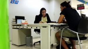 Un ciutadà atén les explicacions d'una treballadora del SOC