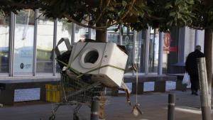 Una rentadora, en un carro de supermercat davant de la Cambra de Comerç de Terrassa