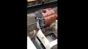 Imagen del momento en el que el hombre, dentro del cubo, es apunto de ser arrojado al camión