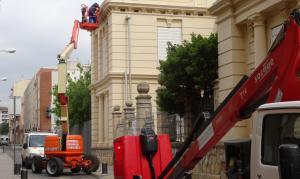 Imatge dels treballs d'instal·lació de la nova il·luminació ornamental a la façana de l'Escola Pompeu Fabra de Reus