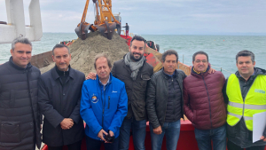 Pla americà de representants de l'Ajuntament de Deltebre i de Ports davant l'embarcació amb que s'ha fet el dragatge