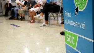 Sala interior d'una oficina del Servei d'Ocupació de Catalunya (SOC) on es veuen els peus d'uns aturats asseguts a la sala d'espera