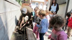 Un avi, ajudant els infants d'El Cuc amb l'hort