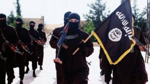 Un militante de Estado Islámico exhibe una bandera en Raqa-
