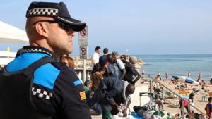 Un policia vigila els venedors del top manta.