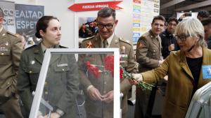 Una dona de la plataforma 'Desmilitaritzem l'Educació' lliura un clavell als militars presents a la Fira d'FP de Lleida