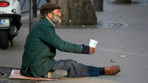 Una persona sense llar, demanant almoïna al carrer.