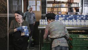 Unes voluntàries preparen el paquet alimentari per emportar del cap de setmana